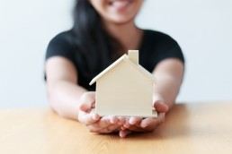 Happy female showing a wooden house to tenants